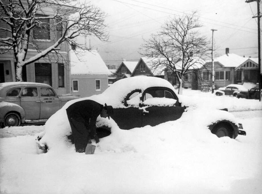 The man in this snowy scene had his car parked near 20th Avenue and East Jefferson Street. The photo was taken Jan. 21, 1943. Reports called it the worst Seattle snow in two decades. (Copyright MOHAI, Seattle Post-Intelligencer Collection, PI28399. Click for reproductions.) Photo: -