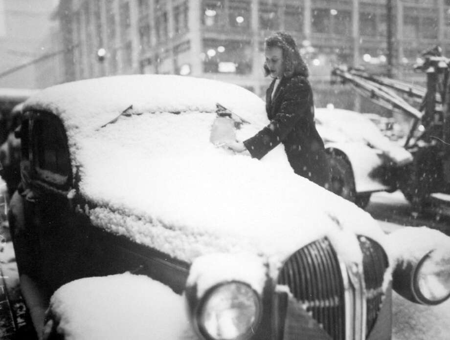 This picture from Feb. 1, 1947 shows Kathy Gustafson clearing snow from her car after a storm. Seattle was halted by the snow that year, but it wasn't quite as bad as the storm of four years prior. (Copyright MOHAI, Seattle Post-Intelligencer Collection, PI28423. Click for reproductions.) Photo: -