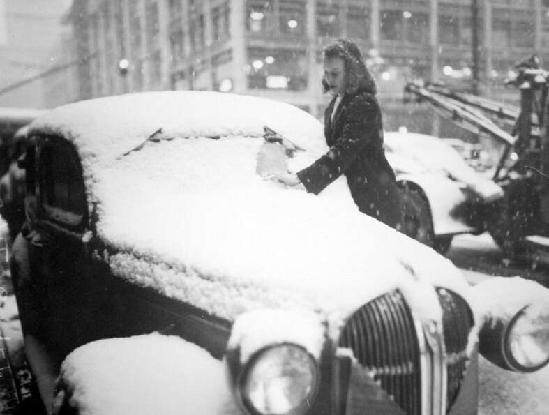 This picture from Feb. 1, 1947 shows Kathy Gustafson clearing snow from her car after a storm. Seatt