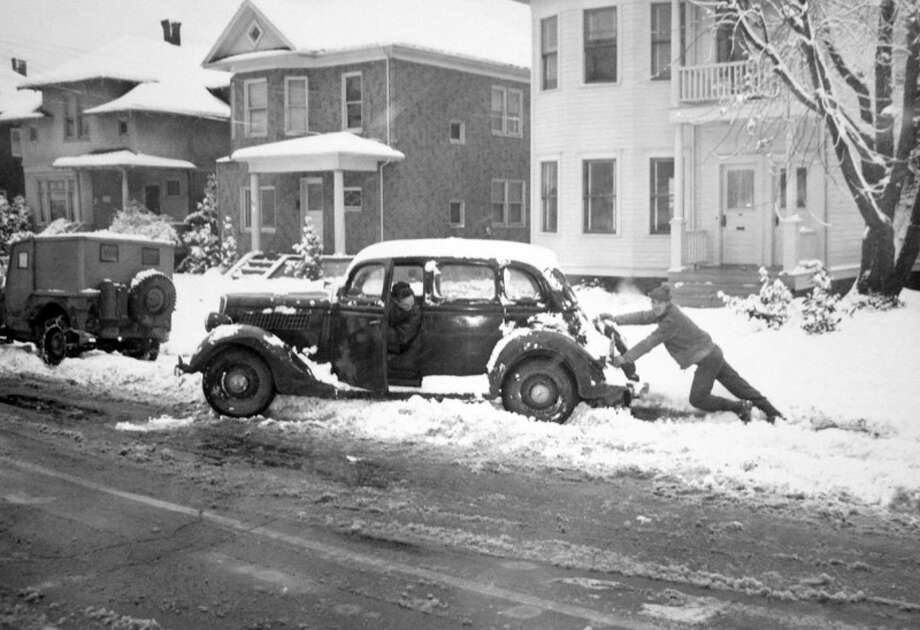 Here's another picture from the Nov. 1946 Seattle snowstorm. Driver Ed Prendergast was stuck and his buddy Dick Francisco was pushing him. (Copyright MOHAI, Seattle Post-Intelligencer Collection, PI28412. Click for reproductions.) Photo: -