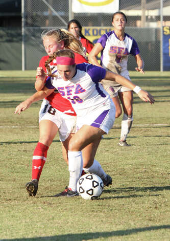 Lamar's Megan Campbell, left, fights for the ball during Lamar's 2-1 loss to Stephen F. Austin Sunday in the Southland Conference tournament championship game in Lake Charles, La. (Matt Billiot/Special to the Enterprise)