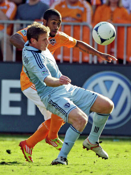 Sporting Kansas City's Jacob Peterson, front, and Houston Dynamo's Corey Ashe work to control the ba