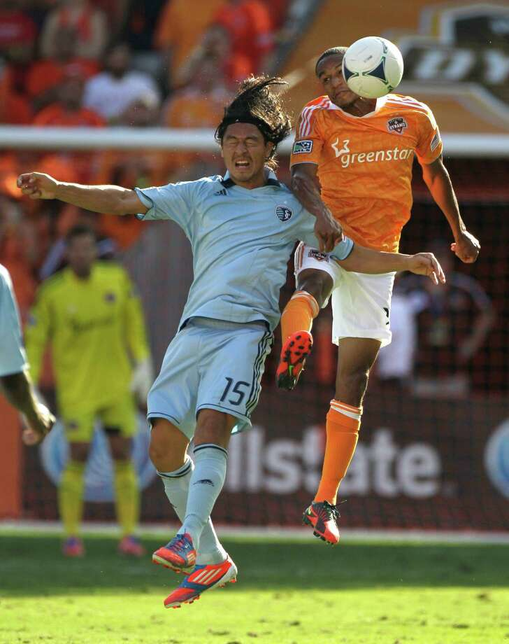 Sporting Kansas City Roger Espinoza, left, Houston Dynamo Ricardo Clark, right, take to the air for ball during the MLS Eastern Conference semifinal at the BBVA Compass Stadium Sunday, Nov. 4, 2012, in Houston. Photo: Melissa Phillip, Houston Chronicle / © 2012 Houston Chronicle