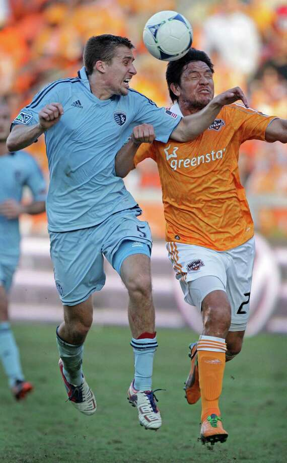Sporting Kansas City Matt Besler, left, and Houston Dynamo Brian Ching, right, tangle for the ball during second half of the MLS Eastern Conference semifinal at the BBVA Compass Stadium Sunday, Nov. 4, 2012, in Houston. Photo: Melissa Phillip, Houston Chronicle / © 2012 Houston Chronicle
