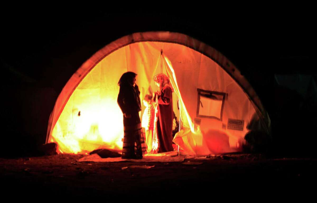 A Syrian family that fled the violence in their village sets up a fire Sunday inside their tent at a camp in the Syrian village of Atma, near the Turkish border. The bloody conflict is claiming more than 100 lives a day.