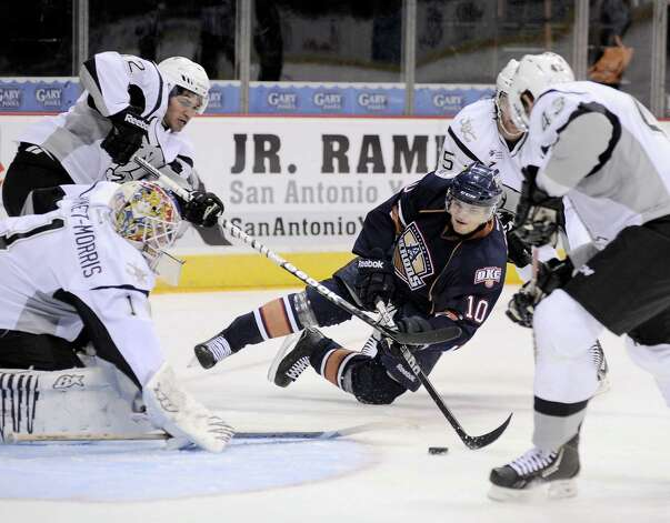 San Antonio Rampage goaltender Dov Grumet-Morris (1) makes a save on a shot by Oklahoma City Barons' Teemu Hartikainen (10), made as he is taken down by Rampage's Colby Robak, right rear, Nolan Yonkman, right, and Jared Gomes, during the first period of an AHL hockey game, Sunday, Nov. 4, 2012, in San Antonio. Photo: Darren Abate, Pressphotointl.com / Darren Abate/pressphotointl.com