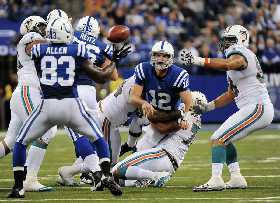 The Colts' Andrew Luck (12) tosses a pass to Dwyane Allen while being tackled in the fourth quarter. Photo: Jim Rassol, MBR / Sun Sentinel