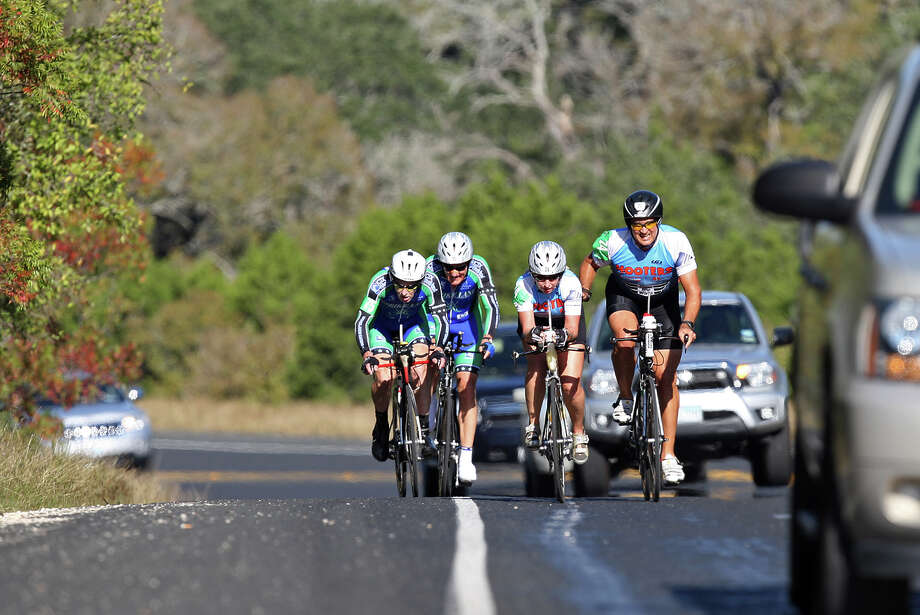 Cyclists ride a 13% grade hill along FM 306 as they compete in the Two-Person Team Trials of the Tour de Gruene, Sunday, Nov. 4, 2012. The event was the last of the two-day time trials. Teams competed in a 26.6-mile course along River Road near Gruene and along FM 306. Photo: Jerry Lara, Express-News / © 2012 San Antonio Express-News
