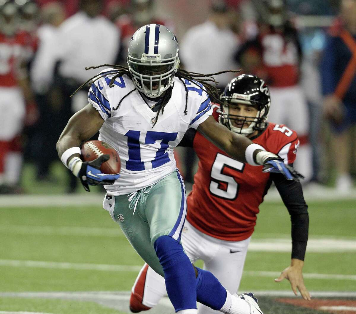 Dallas Cowboys wide receiver Dwayne Harris (17) breaks away from Atlanta Falcons punter Matt Bosher (5) as he returns a punt during the first half of an NFL football game Sunday, Nov. 4, 2012, in Atlanta. (AP Photo/Chuck Burton)