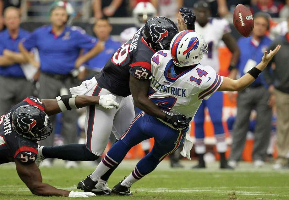 Bills quarterback Ryan Fitzpatrick (14) fumbles the ball as he his hit by Texans linebacker Whitney Mercilus (59) during the fourth quarter. Photo: Nick De La Torre, Houston Chronicle / © 2012  Houston Chronicle