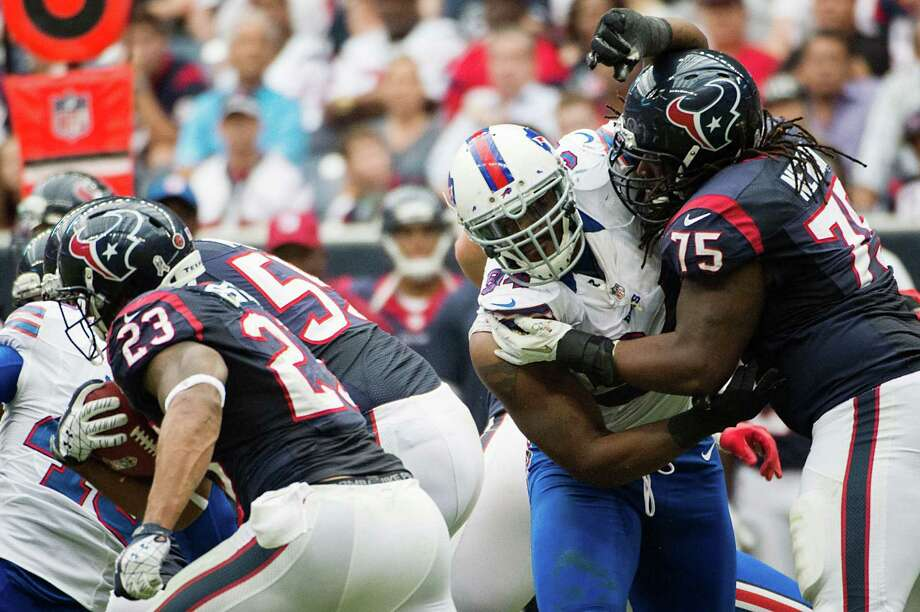 Texans running back Arian Foster (23) hits a hole as tackle Derek Newton (75) makes a block against Bills defensive end Mario Williams (94) during the second half. Photo: Smiley N. Pool, Houston Chronicle / © 2012  Houston Chronicle