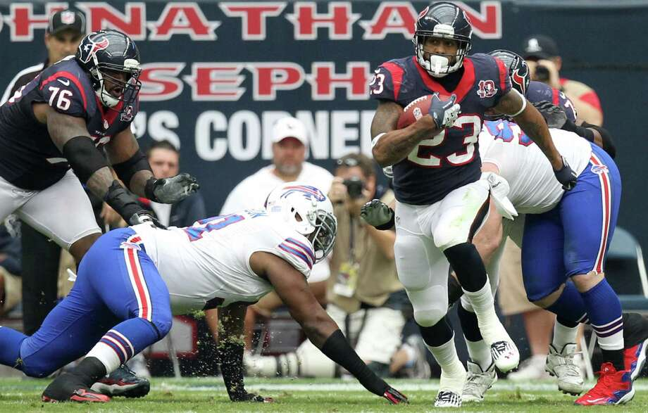 Texans running back Arian Foster (23) runs through the Buffalo Bills defense during the first quarter. Photo: Nick De La Torre, Houston Chronicle / © 2012  Houston Chronicle