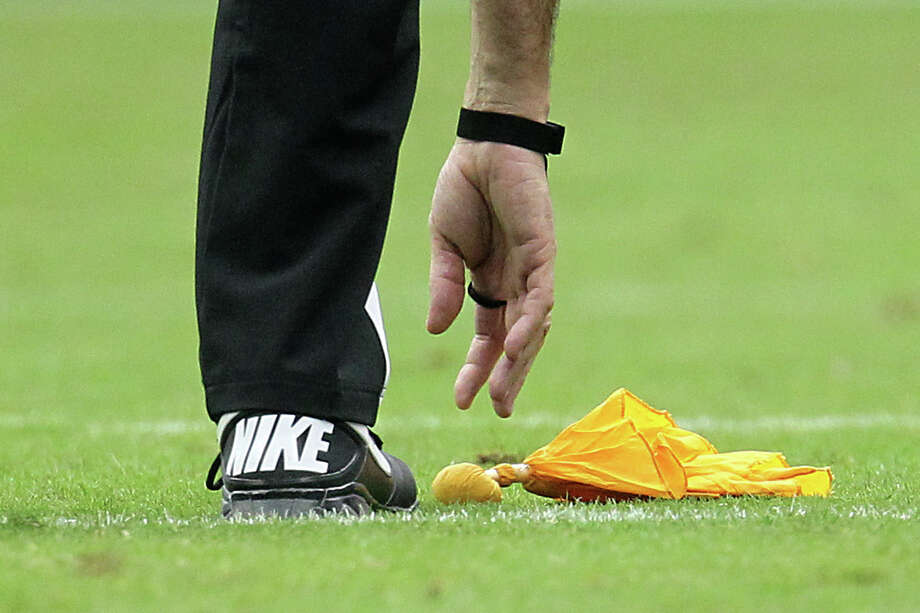 A referee reaches for a flag on the ground after a penalty was called during the second quarter. Photo: Karen Warren, Houston Chronicle / © 2012  Houston Chronicle