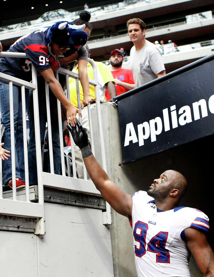 Bills defensive end Mario Williams offers high fives to a Texans fans after the game. Photo: Nick De La Torre, Houston Chronicle / © 2012  Houston Chronicle