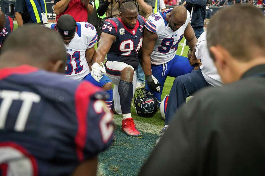 Texans defensive end Antonio Smith  and Bills defensive end Mario Williams hold hands in prayer after the Texans victory. Photo: Smiley N. Pool, Houston Chronicle / © 2012  Houston Chronicle