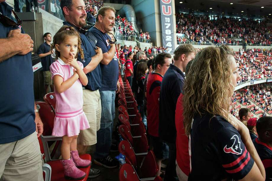Caymin Nolan, 4, stands with her father Jason Nolan during the playing of the national anthem before the Texans game against the Buffalo Bills at Reliant Stadium. Photo: Smiley N. Pool, Houston Chronicle / © 2012  Houston Chronicle