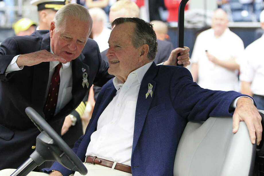 Former President George H.W. Bush chatswith Former Secretary of State James A. Baker before the coin toss. Photo: Karen Warren, Houston Chronicle / © 2012  Houston Chronicle