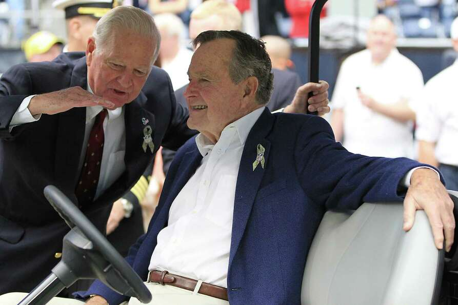 Former President George H.W. Bush chatswith Former Secretary of State James A. Baker before the coin