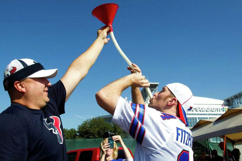 Texans fan Pete Matuszewski, left, holds up a beer funnel for Bills fan Dan Lutman while tailgating outside Reliant Stadium. Photo: Brett Coomer, Houston Chronicle / © 2012  Houston Chronicle