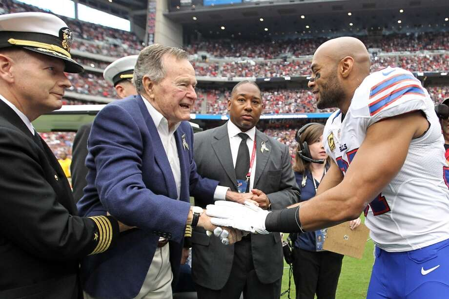 Former President George H.W. Bush  shakes hands with Buffalo Bills strong safety George Wilson before the coin toss. (Karen Warren / Houston Chronicle)