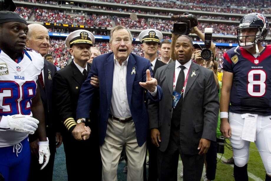 Former President George H.W. Bush flips the coin before the Houston Texans game against the Buffalo Bills. (Brett Coomer / Houston Chronicle)