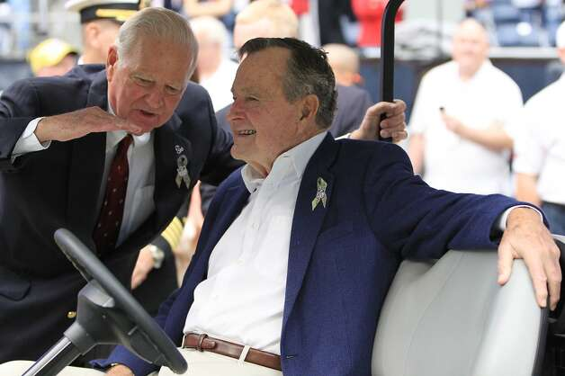 Former President George H.W. Bush chatswith Former Secretary of State James A. Baker before the coin toss. (Karen Warren / Houston Chronicle)