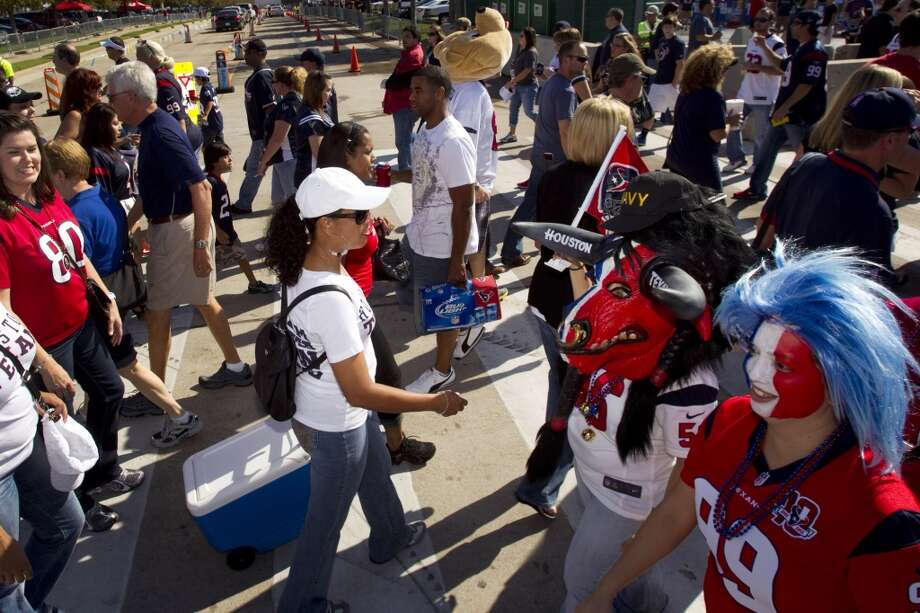 Fans walk in the parking lot outside Reliant Stadium before the Texans game against the Bills. (Brett Coomer / Houston Chronicle)