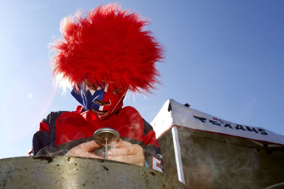 Texans fan Jake Borowski checks the temperature on a basket of wings while tailgating outside Reliant Stadium. (Brett Coomer / Houston Chronicle)