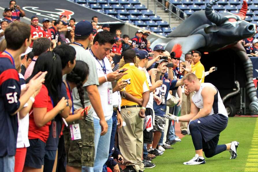 Texans defensive end J.J. Watt greets fans on the sidelines before the game. (Karen Warren / Houston