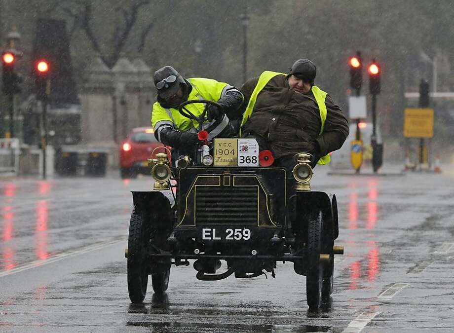 Driver Andre Convents, left, and his co-driver, name not available, check their 1904 Siddeley car after it broke down during the London to Brighton Veteran Car Run, London, Sunday, Nov. 4, 2012. Over 500 pre-1905 vehicles made their way on the historic 60-mile run from Hyde Park in London to coastal Brighton in southern England, in the world's longest running motoring celebration spanning 116 years. All vehicles must be driven at an average speed of no more than 20mph and, in case of breakdowns, outside assistance is only permitted at designated locations. (AP Photo/Lefteris Pitarakis) Photo: Lefteris Pitarakis, Associated Press