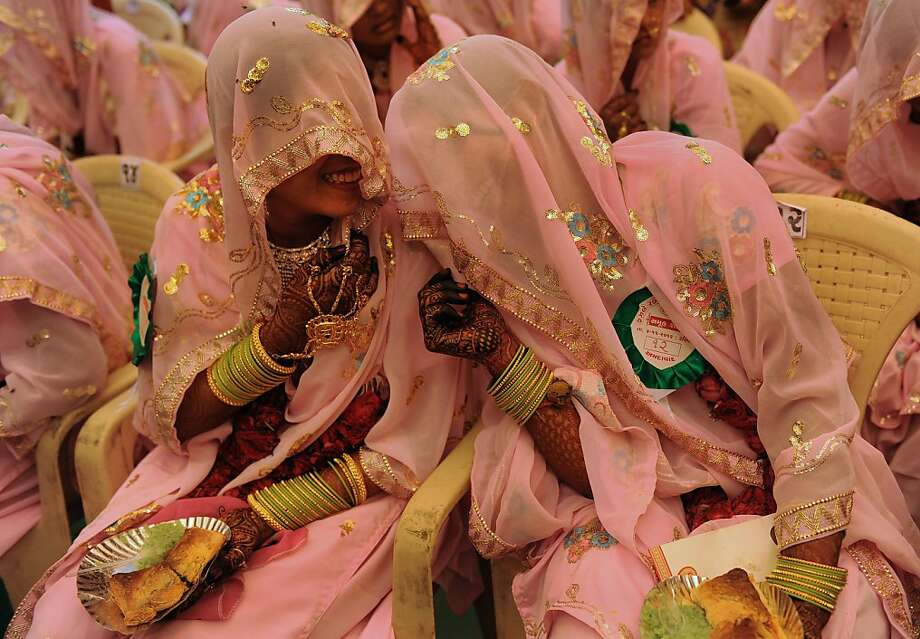 Indian Muslim brides chat as they wait for the start of a mass wedding ceremony in Ahmedabad on November 4, 2012. Some 47 Muslim couples participated in a mass wedding ceremony organised by The Fazale Rabbi Samuh Lagna Committee. AFP PHOTO/Sam PANTHAKYSAM PANTHAKY/AFP/Getty Images Photo: Sam Panthaky, AFP/Getty Images