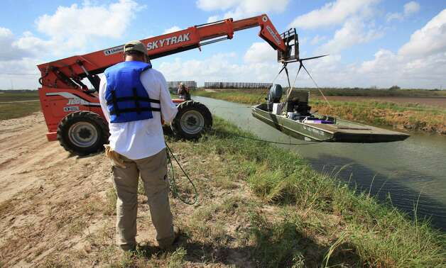 Environmental scientists hoist a boat from a Donna Reservoir Canal system where they are taking water samples to check for PCB's, near Donna, TX. Tuesday, Sept. 25, 2012. Photo: BOB OWEN, San Antonio Express-News / © 2012 San Antonio Express-News