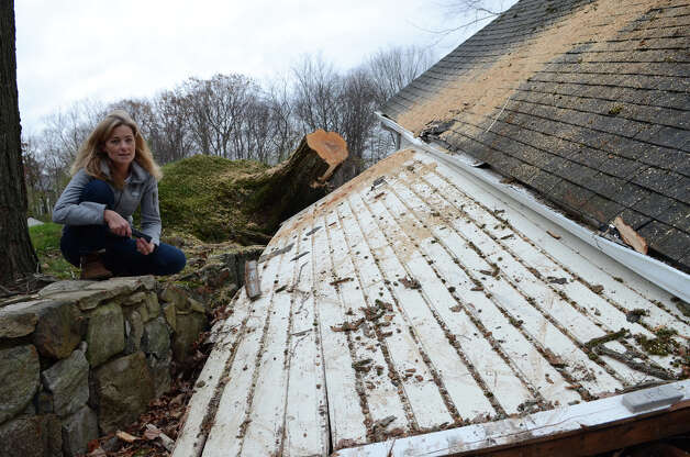 Michelle Morris sits on the rock wall next to her collapsed garage on Hunting Ridge Rd. in Stamford, on Thursday, Nov. 1, 2012. Photo: Amy Mortensen / Connecticut Post Freelance