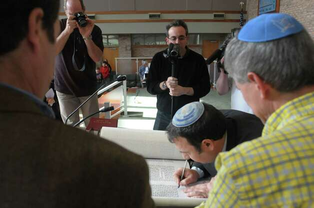 Rabbi Gustavo Surazski, center, from Israel writes the word Israel as he hand letters the last word in a Torah at Congregation Ohav Shalom during their Torah Dedication Ceremony on Sunday, Nov. 4, 2012 in Albany, NY.  The congregation raised money to pay for the new sacred Torah to be written out by Rabbi Surazski. Rabbi Surazski spent a year hand-lettering the sacred scroll.  This Torah is  the first-ever scroll commissioned by the 101-year-old congregation.  The Torah contains the 5 books of the Old Testament.  (Paul Buckowski / Times Union) Photo: Paul Buckowski  / 00019945A