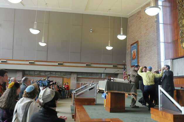 Rabbis and congregation members dance after the final word was written in their new Torah at Congregation Ohav Shalom during their Torah Dedication Ceremony on Sunday, Nov. 4, 2012 in Albany, NY.  The congregation raised money to pay for the new sacred Torah to be written out by Rabbi Gustavo Surazski from Israel.  Rabbi Surazski spent a year hand-lettering the sacred scroll.  This Torah is  the first-ever scroll commissioned by the 101-year-old congregation.  The Torah contains the 5 books of the Old Testament.  (Paul Buckowski / Times Union) Photo: Paul Buckowski  / 00019945A