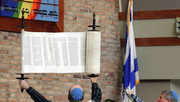The new Torah is held up as they begin the process of rolling it up at Congregation Ohav Shalom during their Torah Dedication Ceremony on Sunday, Nov. 4, 2012 in Albany, NY.  The congregation raised money to pay for the new sacred Torah to be written out by Rabbi Gustavo Surazski from Israel.  Rabbi Surazski spent a year hand-lettering the sacred scroll.  This Torah is  the first-ever scroll commissioned by the 101-year-old congregation.  The Torah contains the 5 books of the Old Testament.  (Paul Buckowski / Times Union) Photo: Paul Buckowski  / 00019945A