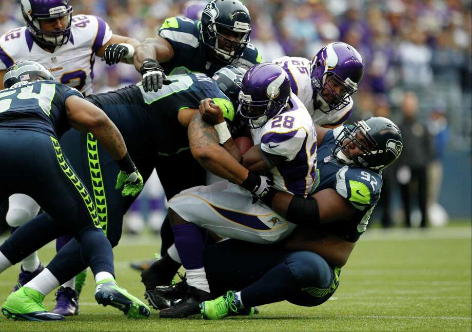 Minnesota Vikings' Adrian Peterson (28) is tackled by Seattle Seahawks' Brandon Mebane (92) in the first half of an NFL football game, Sunday, Nov. 4, 2012, in Seattle. Photo: AP