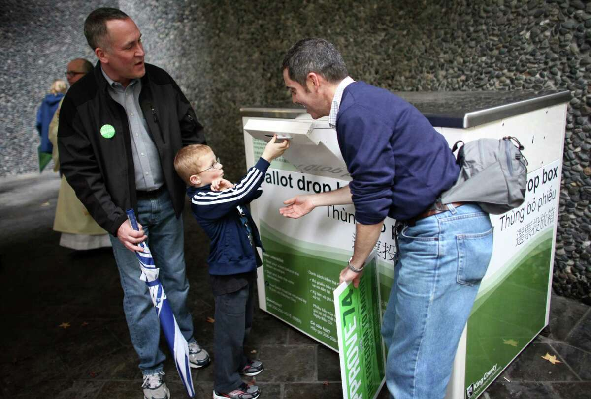 Isaac Liljegren, 6, drops the ballots of his dads' Eric Liljegren, left, and Scott Shiebler into a box outside the King County Administration Building as people in the faith community participate in a pro-Referendum 74 march and rally on Sunday, November 4, 2012 in Seattle. Hundreds of marriage equality supporters marched from Seattle's Central Lutheran Church to the King County Administration Building where they dropped their ballots in the drop box.