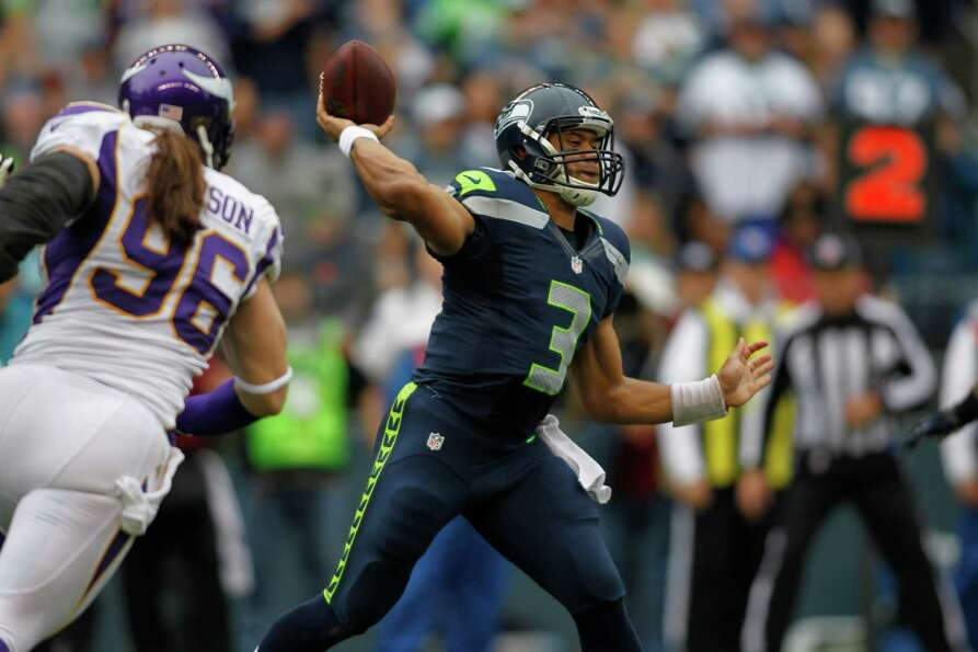 Seattle Seahawks quarterback Russell Wilson makes a pass as Minnesota Vikings' Brian Robison defends