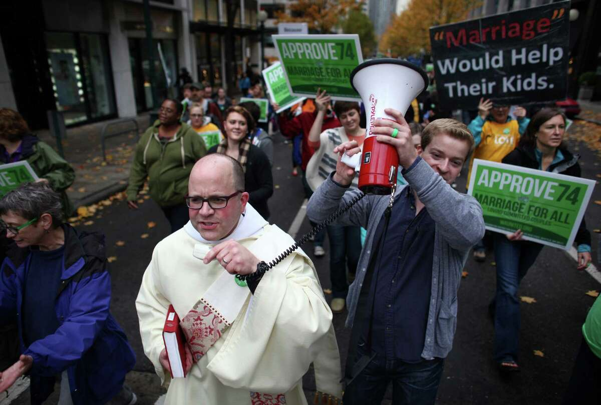 Episcopal Deacon Stephen Crippen leads a chant as people in the faith community participate in a pro-Referendum 74 march and rally on Sunday, November 4, 2012 in Seattle. Hundreds of marriage equality supporters marched from Seattle's Central Lutheran Church to the King County Administration Building where they dropped their ballots in a drop box.