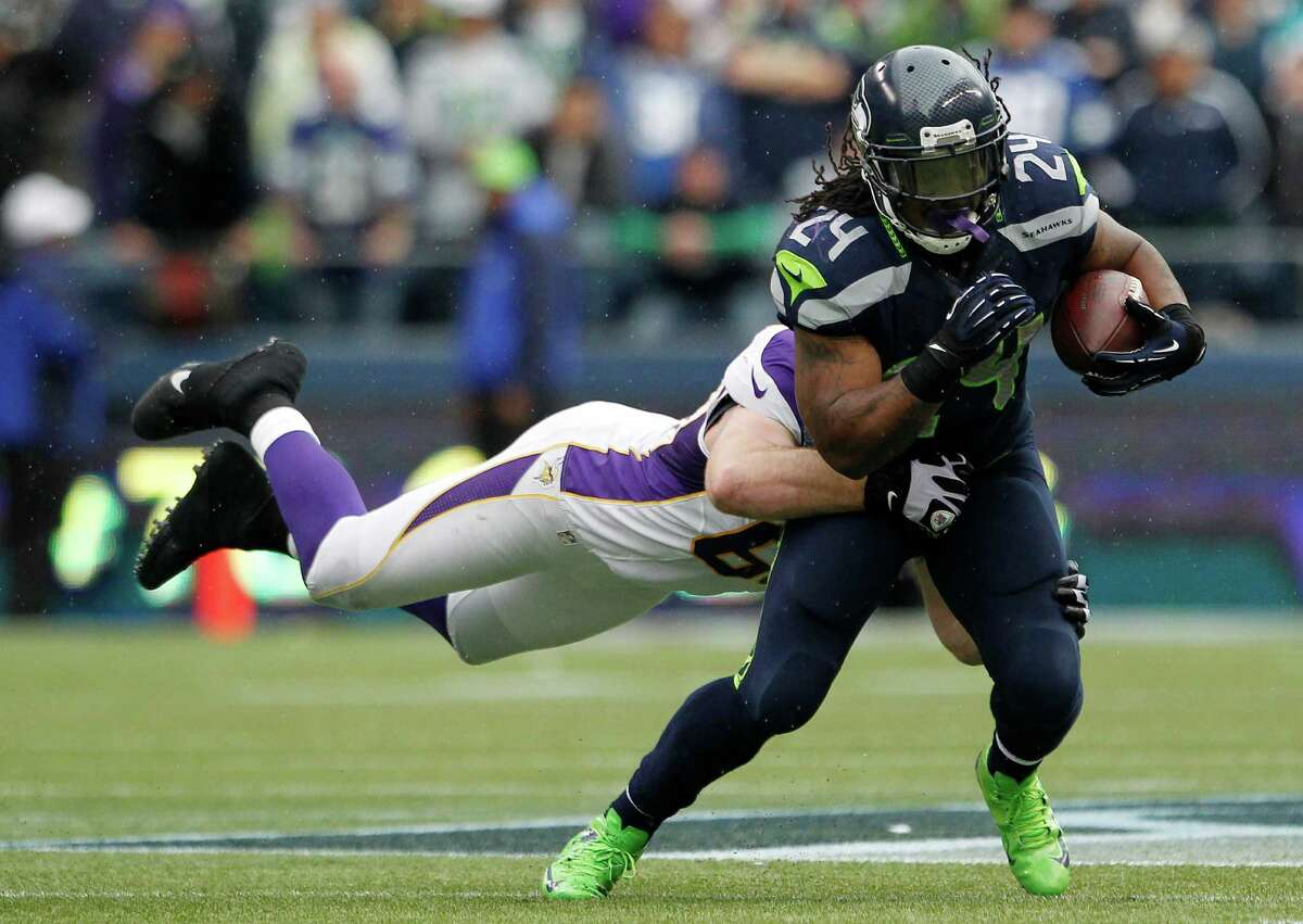 Seattle Seahawks' Marshawn Lynch (24) carries Minnesota Vikings' Jared Allen with him as he rushes in the second half of an NFL football game, Sunday, Nov. 4, 2012, in Seattle. The Seahawks won 30-20.