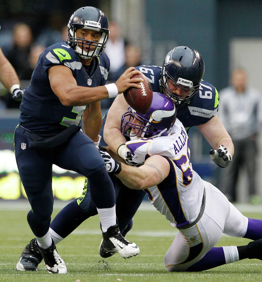 Seattle Seahawks quarterback Russell Wilson, left, scrambles as Minnesota Vikings' Jared Allen is blocked by Seahawks' Paul McQuistan (67) during the second half of an NFL football game, Sunday, Nov. 4, 2012, in Seattle. Photo: AP