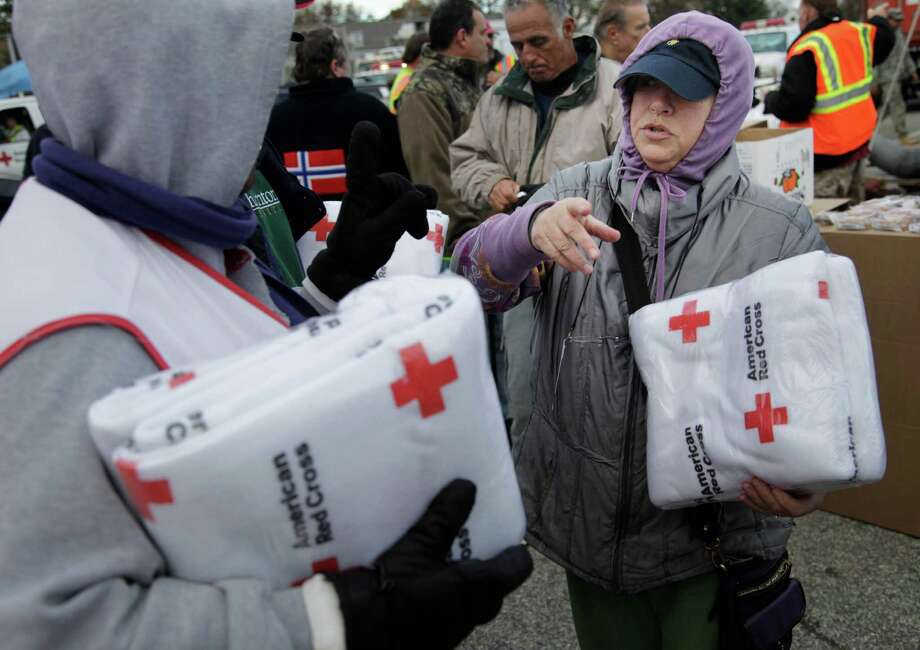 Galina Quacinella, right, gets some blankets for herself and her husband at a Red Cross aid station in Staten Island, New York, Sunday, Nov. 4, 2012. With overnight temperatures sinking into the 30s, hundreds of thousands of homes and businesses are still without electricity in the aftermath of Superstorm Sandy. (AP Photo/Seth Wenig) Photo: Seth Wenig