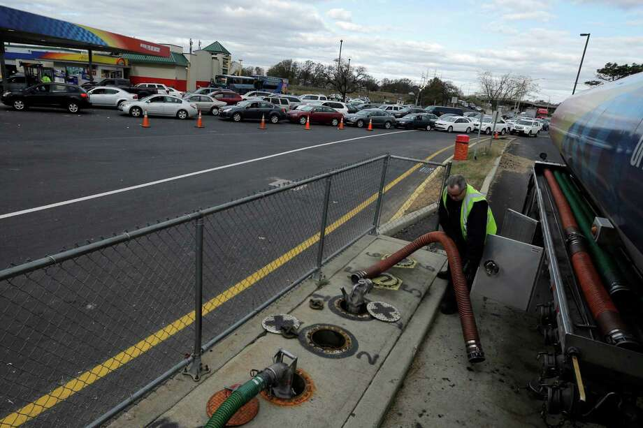 Thomas Reilly, of Central Islip, NY, prepares to unload fuel at a packed service area along the New Jersey Turnpike, Sunday, Nov. 4, 2012, in Woodbridge, N.J. About 1 million homes and businesses across New Jersey are still without electricity due to Superstorm Sandy on Sunday, and officials say many of those customers may not have service restored until Wednesday. (AP Photo/Matt Slocum) Photo: Matt Slocum