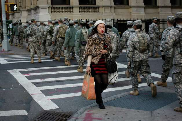 A woman with her groceries passes a group of National Guardsmen as they march up 1st Avenue towards the 69th Regiment Armory, Saturday, Nov. 3, 2012, in New York. National Guardsmen remain in Manhattan as the city begins to move towards normalcy following Superstorm Sandy earlier in the week. (AP Photo/ John Minchillo) Photo: John Minchillo