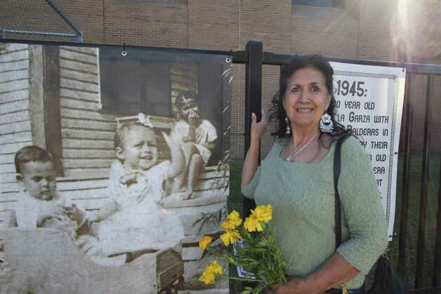 Maria Ester Caldera stands next to one of the new fotobanners along Guadalupe Street. Caldera is the young pictured sitting on the steps. Photo: Noi Mahoney/ Southside Reporter