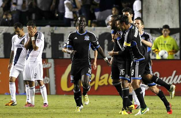 San Jose Earthquakes forward Chris Wondolowski (8) and forward Simon Dawkins (10), of England, celebrate defender Victor Bernardez, second from right, of Honduras, free kick for a goal as Los Angeles Galaxy midfielder Marcelo Sarvas (8), of Brazil, hides his face with midfielder Juninho (19), of Brazil, dejected during the extra time period of the second half of their MLS playoff soccer match, Sunday, Nov. 4, 2012, in Carson, Calif. Earthquakes won the match 1-0.  (AP Photo/Alex Gallardo) Photo: Alex Gallardo, Associated Press