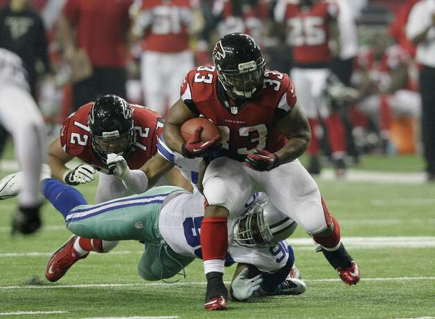 Atlanta Falcons running back Michael Turner (33) gets away from Dallas Cowboys nose tackle Jay Ratliff (90) during the second half of an NFL football game Sunday, Nov. 4, 2012, in Atlanta. (AP Photo/Chuck Burton) Photo: Chuck Burton, Associated Press / AP