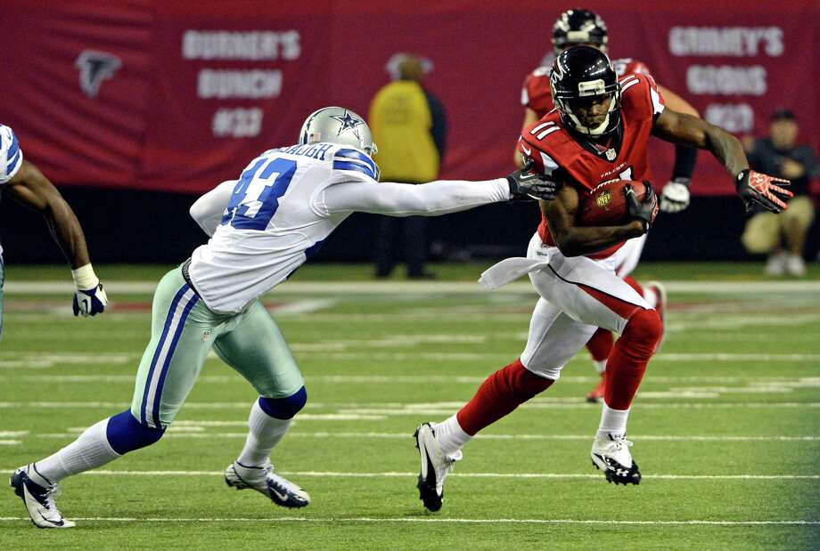 Atlanta Falcons' Julio Jones (11) tries to run past the grasp of Dallas Cowboys' Gerald Sensabaugh (43) during the second half of an NFL football game in Atlanta, Sunday, Nov. 4, 2012. Atlanta won 19-13. (AP Photo/Rich Addicks) Photo: Rich Addicks, Associated Press / FR170246 AP