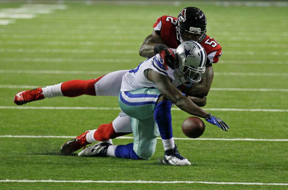 Atlanta Falcons' Akeem Dent, top, knocks the ball away from Dallas Cowboys' Lance Dunbar, bottom, during the second half of an NFL football game in Atlanta, Sunday, Nov. 4, 2012. Atlanta won 19-13. (AP Photo/Chuck Burton) Photo: Chuck Burton, Associated Press / AP